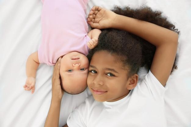Schattige baby en oudere zus op bed