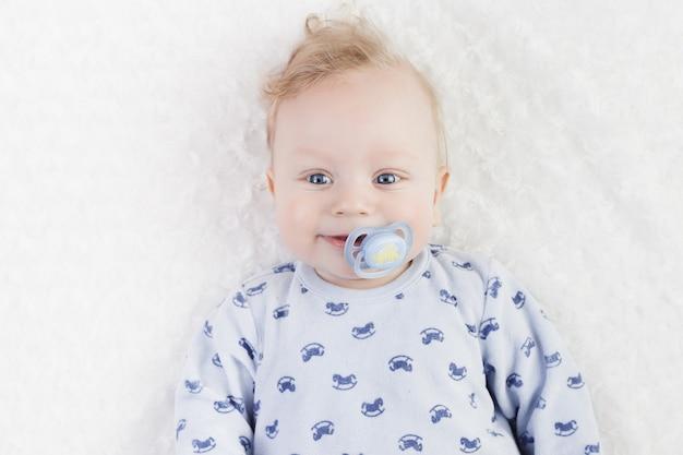 Schattige baby in blauwe pyjama met fopspeen