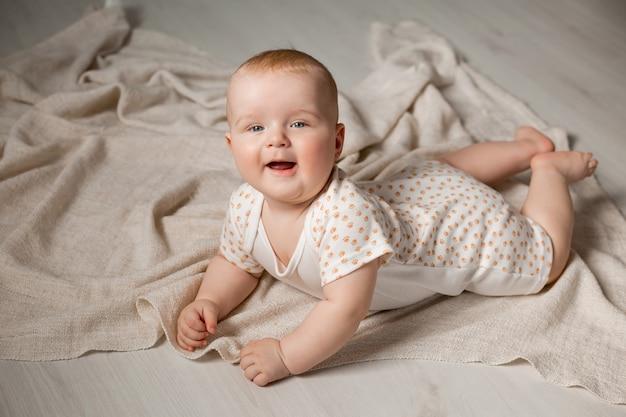 Schattige baby in een bodysuit ligt op zijn buik op de houten vloer met een deken thuis