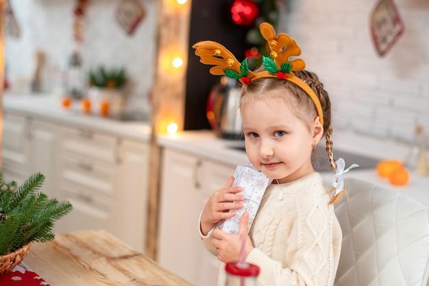 Schattige baby in een lichte trui en haarband met rendierhoorns