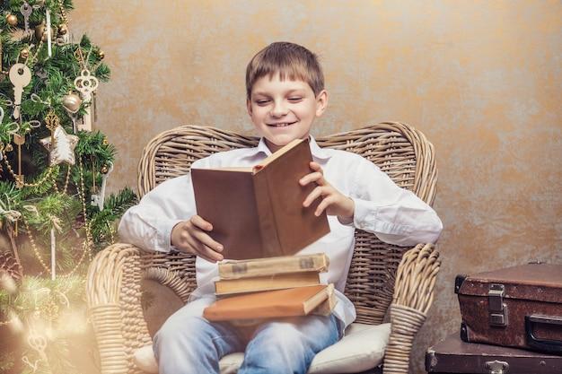 Schattige baby in een stoel die een boek leest in een retro kerstinterieur