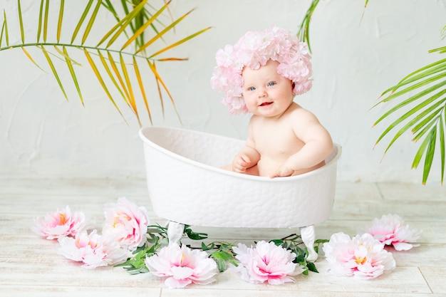Schattige baby in het bad baadt in een bloemenhoed met pioenrozen, het concept van hygiëne en kinderopvang