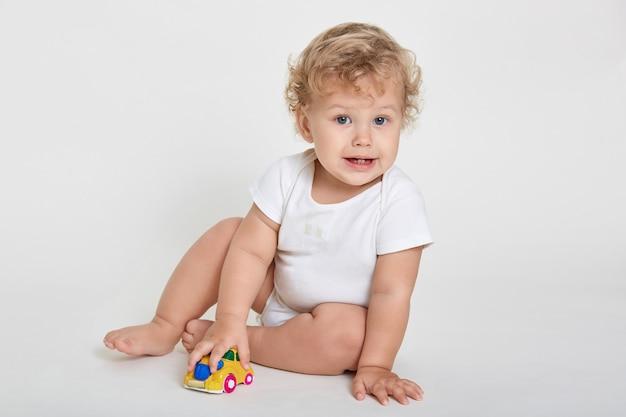 Schattige baby jongen peuter spelen met speelgoedauto binnen