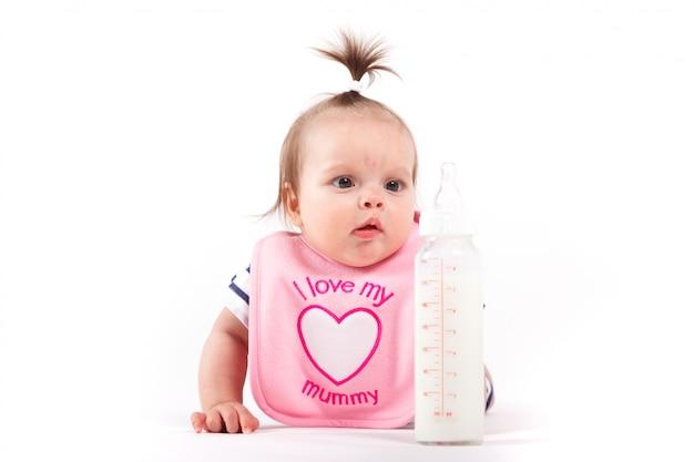 Schattige baby meisje in roze slabbetje met fles
