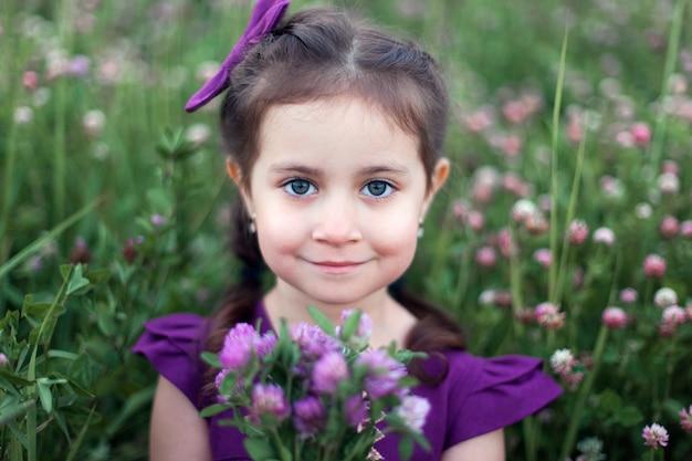 Schattige baby meisje oude bedrijf bloem in weide buitenshuis. jeugd