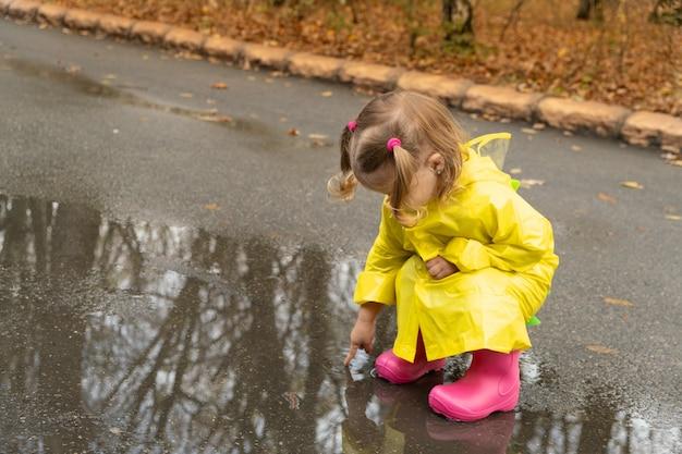 Schattige baby meisje peuter gele stijlvolle regenjas roze rubberen laarzen dragen staande in een plas.