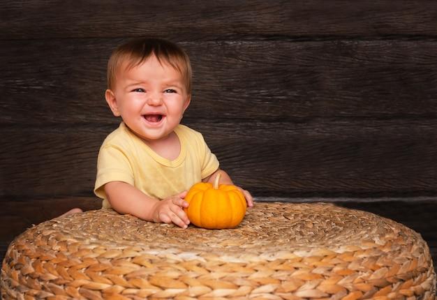 Schattige baby met een kleine oranje pompoen lachend in de buurt van een stro tafel op hout