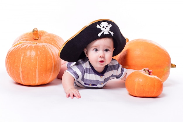 Schattige baby met een piraat hoed op zijn hoofd liggend op zijn buik op
