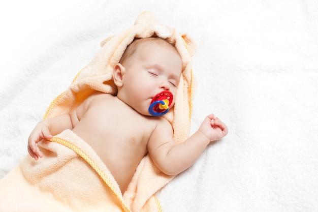 Schattige baby met fopspeen dutje doen.