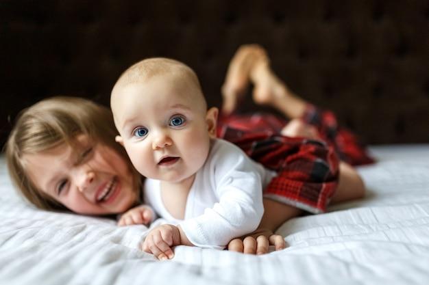 Schattige baby met gelukkige zus op het bed thuis op zoek