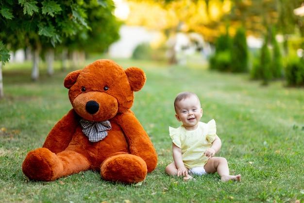 Schattige baby met grote teddybeer op gras of groen gazon in de zomer
