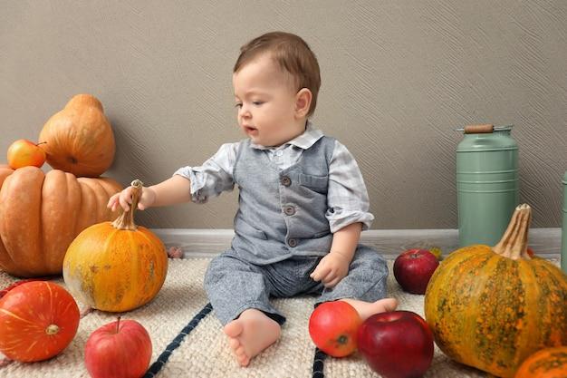 Schattige baby met rijpe pompoenen en appels binnenshuis