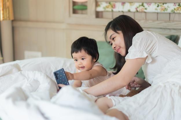 Schattige baby neemt een foto met moeder en zittend op het bed