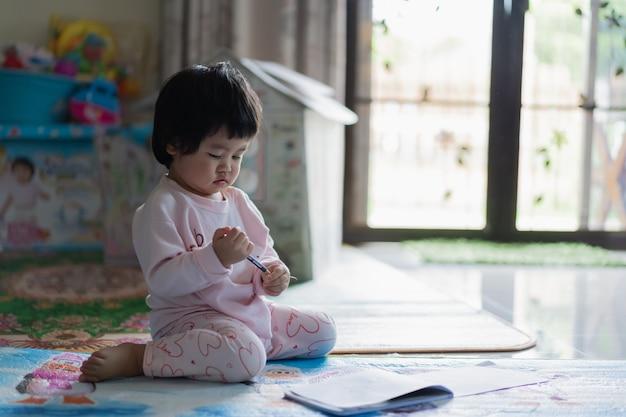 Schattige baby puttend uit het notitieboekje op de vloer