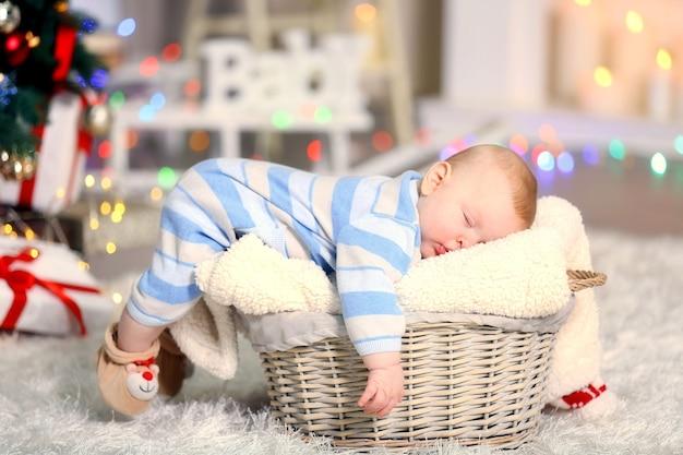 Schattige baby slaapt in versierde rieten mand