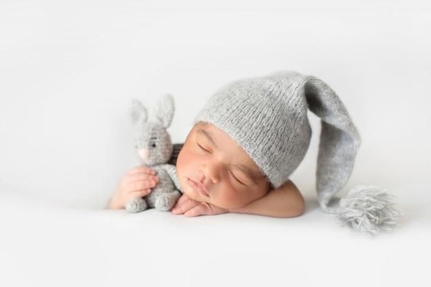 Schattige baby slaapt met grijze gehaakte muts en met speelgoed konijn