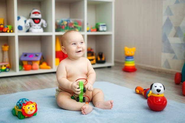 Schattige baby speelt met educatief speelgoed. speelgoed voor jonge kinderen. binnenland van het kinderdagverblijf van een kleine jongen.