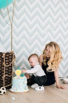 Schattige baby spelen met zijn jonge moeder op het kinderfeestje van zijn eerste verjaardag