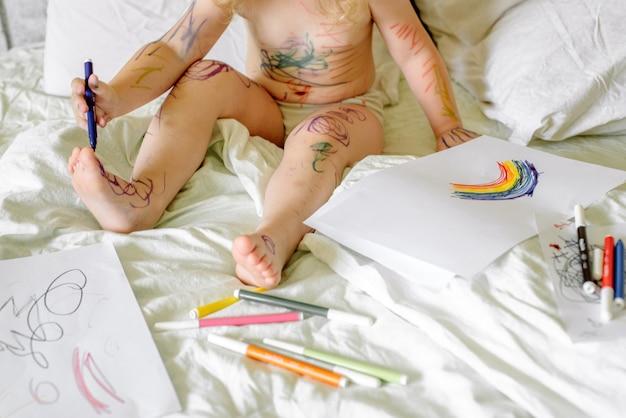Schattige baby tekent met een stift op een wit bed. besmeurde handen en voeten, vuil van de verf. grappig plaatje, grappig kind.