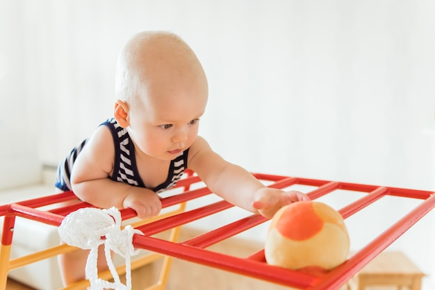 Schattige baby voert gymnastische oefeningen op een houten huis sport complexe trappen en ringen