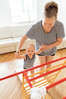 Schattige baby voert gymnastische oefeningen uit op een thuissportcomplex. sportoefeningen voor kinderen. lichamelijke opvoeding van kinderen thuis