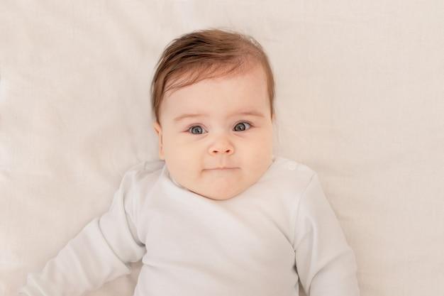 Schattige baby zes maanden liggend in een wieg in een witte romper