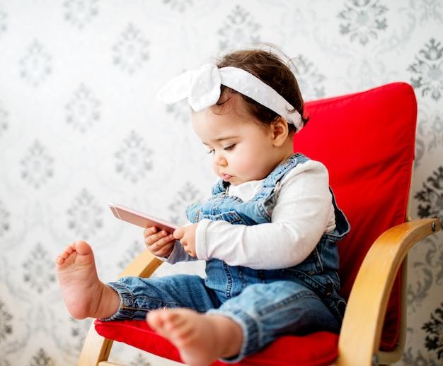 Schattige baby zit in de stoel in de woonkamer en speelt met een smartphone.