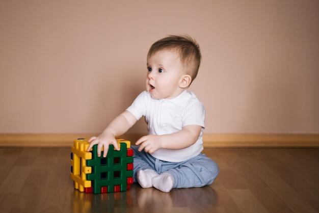 Schattige baby zittend op de vloer van het huis spelen met een veelkleurige kubus