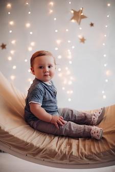 Schattige baby zittend op mooie schommel versierd voor kerstmis.