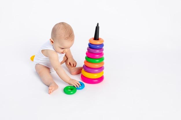 Schattige babyjongen 8 maanden oud spelen met een piramide op wit