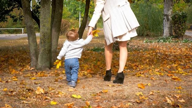 Schattige babyjongen die de hand van de moeder vasthoudt en de eerste stappen zet in het herfstbos of park.