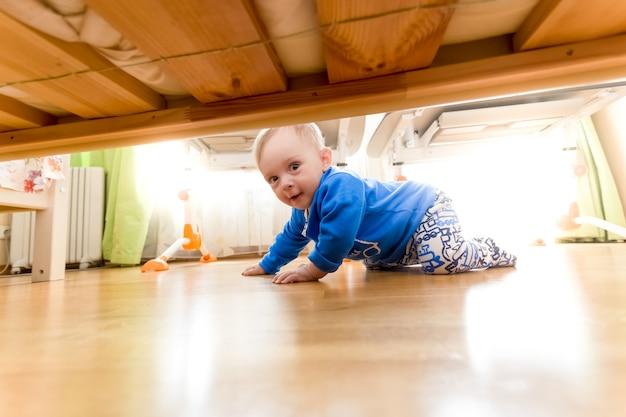 Schattige babyjongen die op de vloer kruipt en onder het bed kijkt