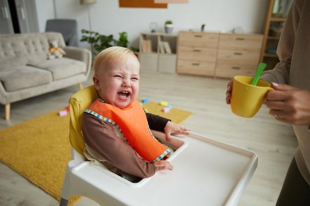Schattige babyjongen dragen slabbetje babystoel zittend terwijl zijn moeder hem voedt in de keuken