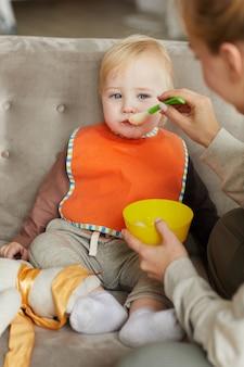 Schattige babyjongen dragen slabbetje zittend op de bank terwijl moeder hem voedt in de kamer