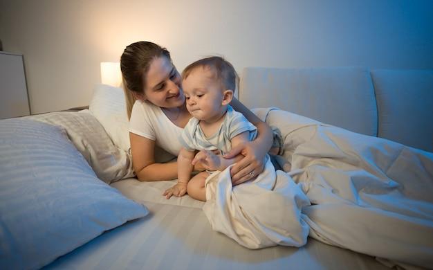Schattige babyjongen en zijn moeder 's avonds laat in bed