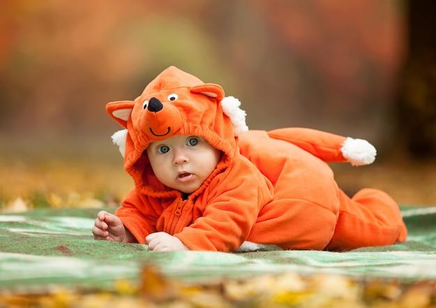 Schattige babyjongen gekleed in vos kostuum in herfst park