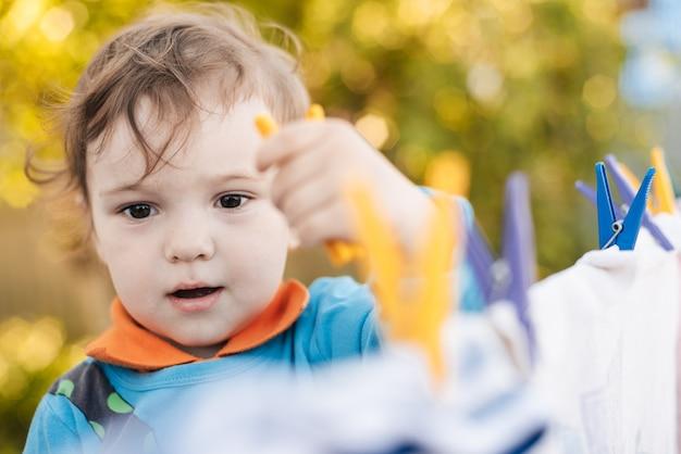 Schattige babyjongen helpt wasserij op te hangen aan een touw met wasknijpers