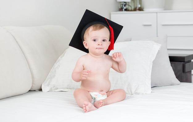 Schattige babyjongen in academische zwarte hoed zittend op bed