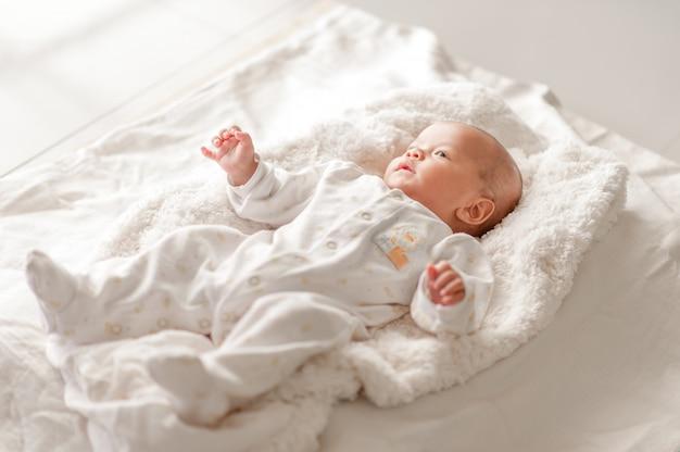 Schattige babyjongen in een wit licht slaapkamer pasgeboren baby is schattig.