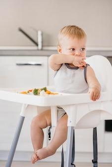 Schattige babyjongen in kinderstoel groenten eten in de keuken