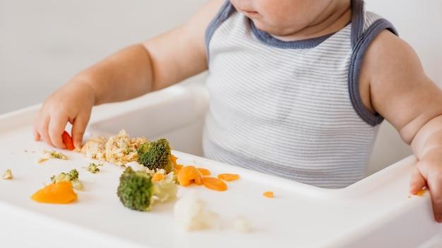 Schattige babyjongen in kinderstoel kiezen wat te eten