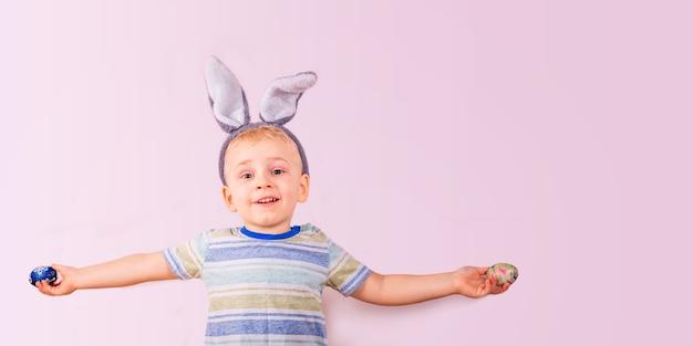 Schattige babyjongen in konijnenoren op hoofd en met gekleurde eieren op roze achtergrond.