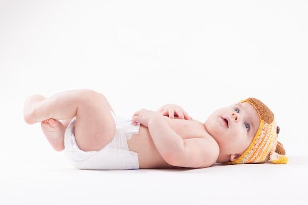 Schattige babyjongen in luier en witte herten hoed
