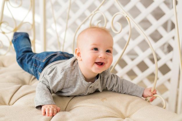 Schattige babyjongen in witte zonnige slaapkamer. pasgeboren kind. kinderdagverblijf voor jonge kinderen. familie ochtend thuis.