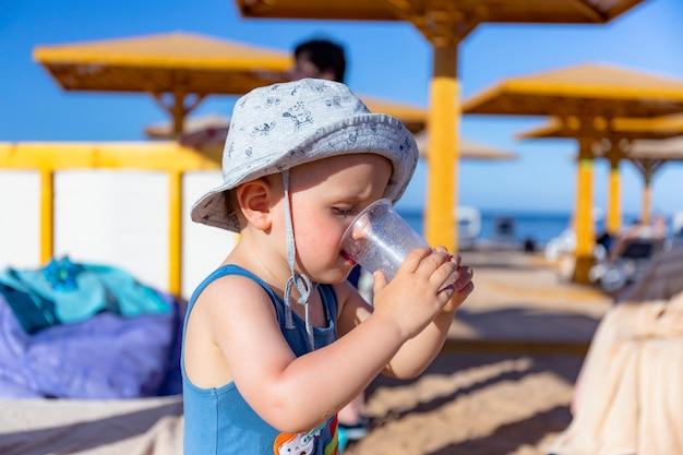 Schattige babyjongen in zomer panama drinkt sap op het strand bij warm weer.