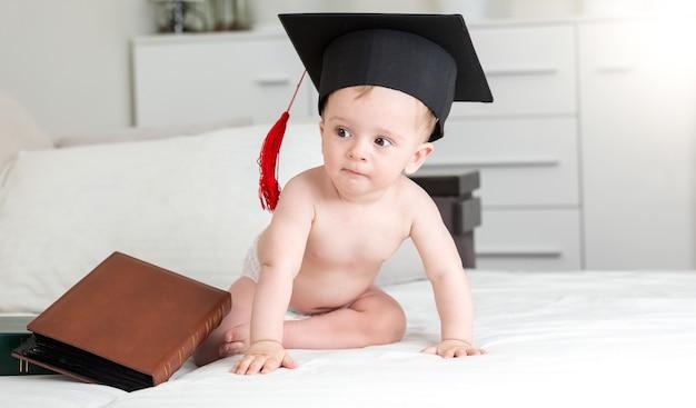 Schattige babyjongen in zwarte afstuderen pet zitplaatsen op de bank