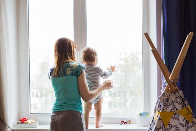 Schattige babyjongen kijkt in het raam