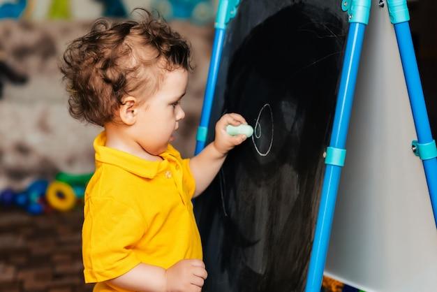 Schattige babyjongen leren tekenen met krijt op een schoolbord