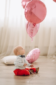 Schattige babyjongen met ballonnen