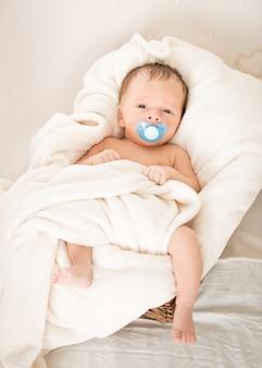 Schattige babyjongen met fopspeen liggend in rieten mand
